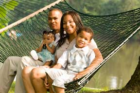 Family on enjoying time together sitting on a hammock.